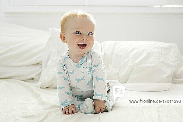 Baby-Junge (6-11 Monate) auf dem Bett liegend