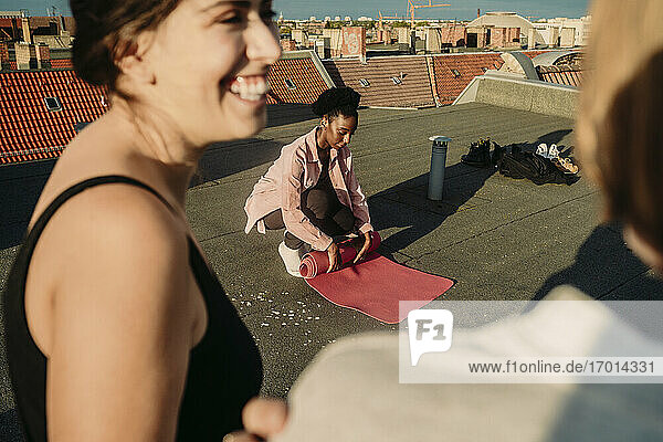 Young female folding exercise mat while friends talking after yoga on rooftop during sunrise