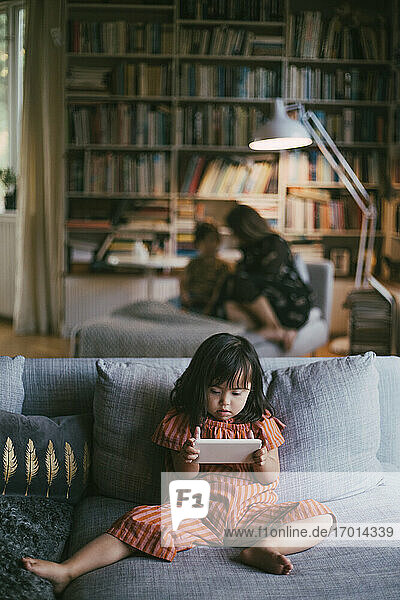 Down syndrome girl using smart phone on sofa at home