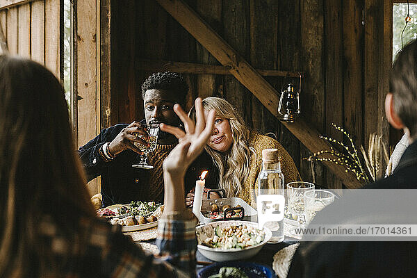 Rear view of woman gesturing while female resting head on friend's shoulder during social gathering