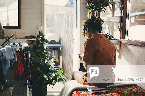 Rear view of woman sitting on bed in houseboat
