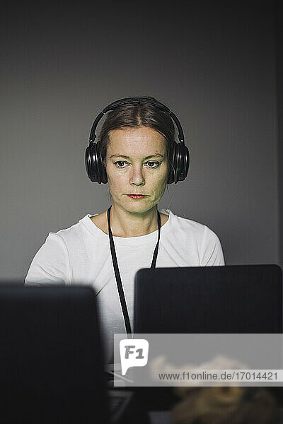 Female IT professional with headphones typing on laptop in creative office