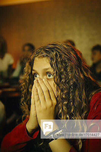 Female sports fan covering mouth with hands while watching TV at night