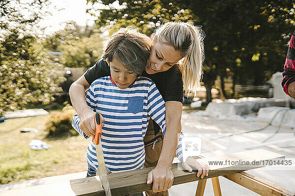 Mother and son cutting wood with hand saw outdoors