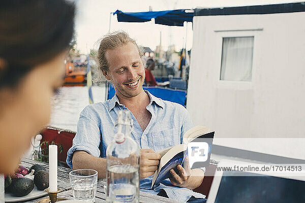 Man smiling while reading book at houseboat