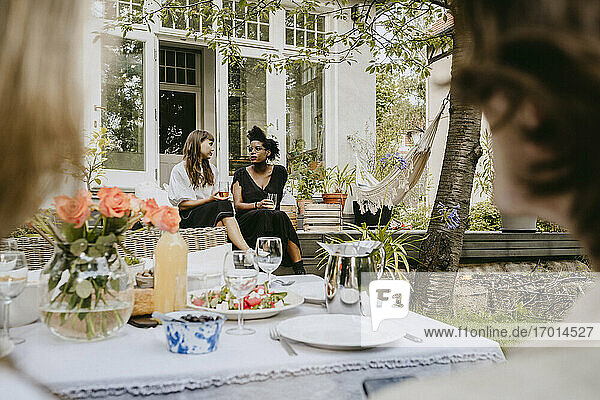 Young women with drinking glass talking while sitting in backyard