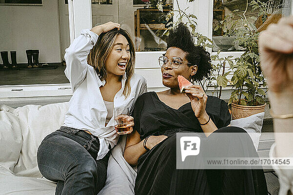 Happy woman with drinking glass talking to female friend while sitting in backyard