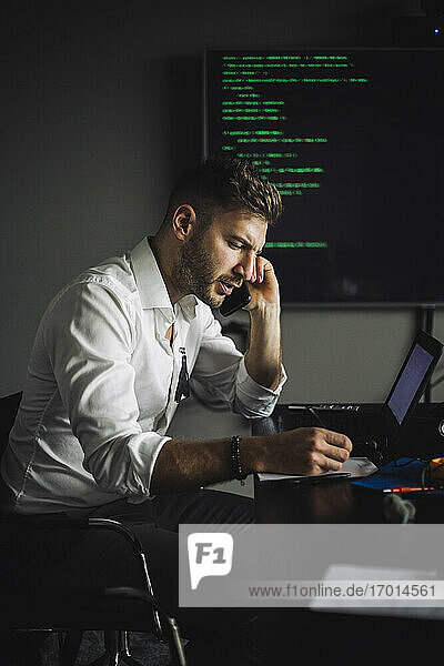 IT professional talking on smart phone while working in creative office