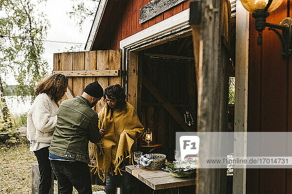 Male and female wrapping shawl on friend while standing outside cottage during social gathering