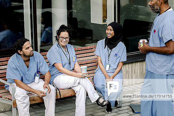Smiling female and male colleagues talking while sitting on bench outside hospital