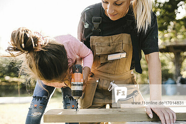 Daughter using drill machine on wooden plank by mother in yard