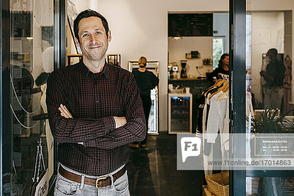 Portrait of male owner with arms crossed standing at doorway of clothing store