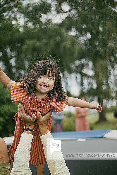 Portrait of smiling down syndrome daughter playing with father on trampoline during summer