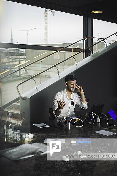 IT professional talking on mobile phone while working in creative office
