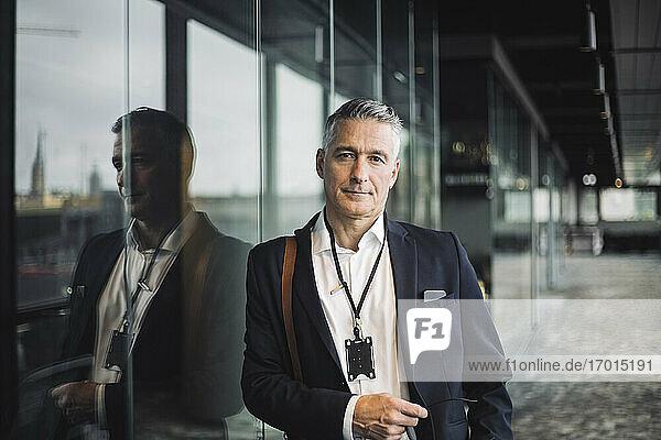 Portrait of entrepreneur leaning on glass window in office