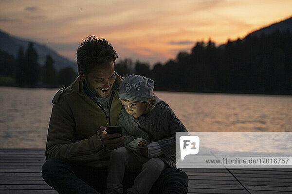Vater und kleine Tochter spielen in der Abenddämmerung mit ihrem Smartphone auf einem Steg am Seeufer