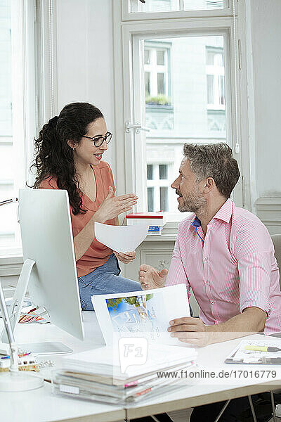 Female entrepreneur discussing with male colleague at desk in meeting