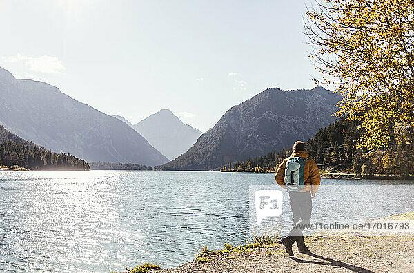 Männlicher Wanderer mit Rucksack am See gegen den Himmel an einem sonnigen Tag Männlicher Wanderer mit Rucksack am See gegen den Himmel an einem sonnigen Tag