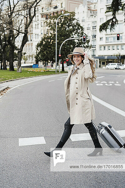 Happy woman with wheeled luggage holding hat while walking on street in city