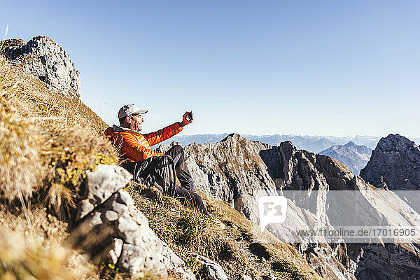 Mature man taking selfie with smart phone while sitting on mountain against clear sky