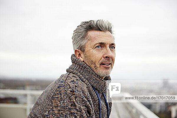 Mature man looking away while standing against sky at rooftop