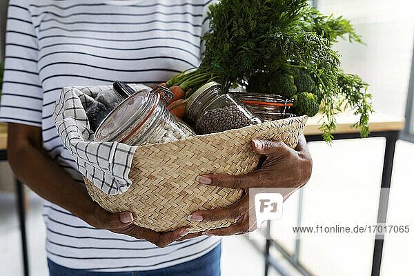 Frau trägt Korb mit frischen Bio-Lebensmitteln in nachhaltiger Verpackung Frau trägt Korb mit frischen Bio-Lebensmitteln in nachhaltiger Verpackung