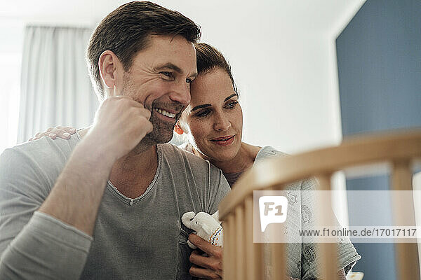 Happy mature couple with stuffed elephant toy looking at crib in bedroom Happy mature couple with stuffed elephant toy looking at crib in bedroom