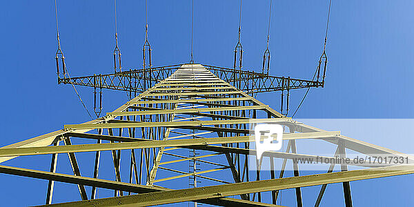 Electricity pylon standing against clear blue sky