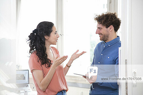 Happy male and female colleagues discussing in office meeting