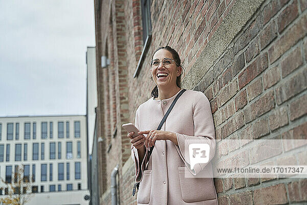Cheerful businesswoman looking away holding smart phone while leaning on brick wall