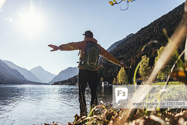 Mature male hiker with arms outstretched looking at lake against clear sky during sunny day