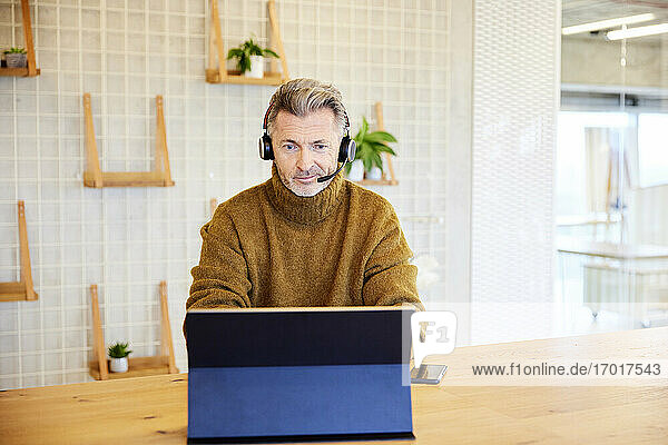Male businessman wearing headset working on digital tablet while sitting at office