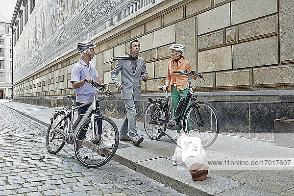 Explorers with electric bicycle looking at man walking with puppy on footpath at Dresden  Germany