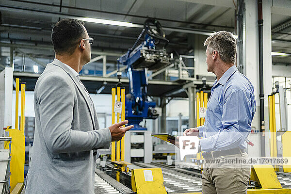 Male professionals with digital tablet looking at machinery equipment in factory