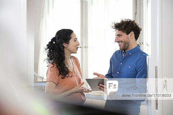 Happy male professional talking with female colleague while holding digital tablet in office meeting