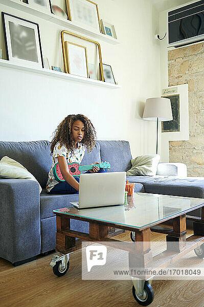 Junge Afroamerikanerin nimmt Online-Unterricht für das Erlernen der Ukulele zu Hause Junge Afroamerikanerin nimmt Online-Unterricht für das Erlernen der Ukulele zu Hause
