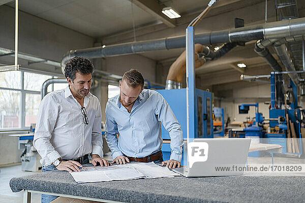 Zwei Zimmerleute sprechen über Dokumente in der Produktionshalle