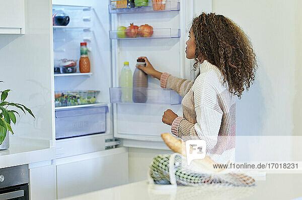 Junge Afro-Frau  die zu Hause Lebensmittel in den Kühlschrank stellt Junge Afro-Frau, die zu Hause Lebensmittel in den Kühlschrank stellt
