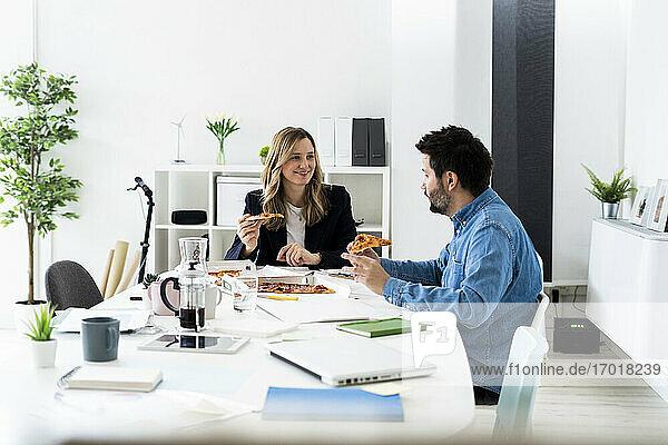 Geschäftsleute essen Pizza und unterhalten sich während der Pause im Büro