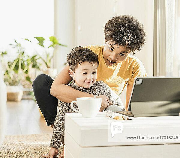 Junge Frau und Junge benutzen ein digitales Tablet  während sie zu Hause sitzen und online lernen Junge Frau und Junge benutzen ein digitales Tablet, während sie zu Hause sitzen und online lernen