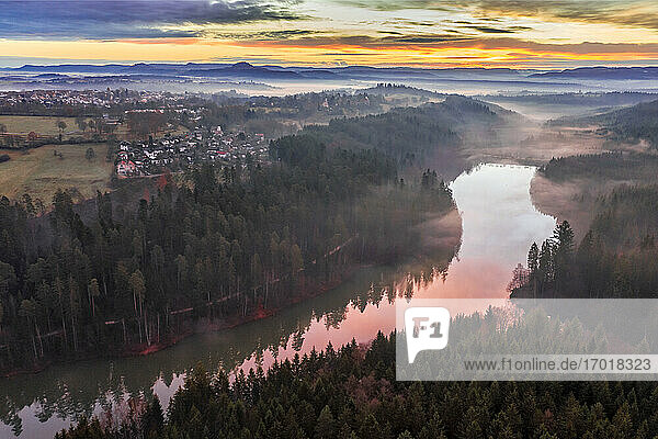 Germany  Baden-Wurttemberg  Drone view of riverside town in Swabian Forest at foggy dawn