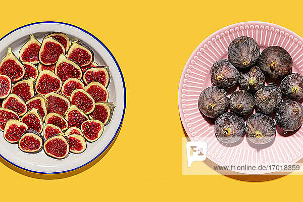 Studio shot of two plates with halved and whole figs