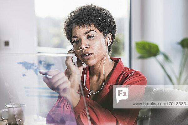 Frau mit Ohrstöpseln  die auf ein transparentes Display zu Hause zeigt Frau mit Ohrstöpseln, die auf ein transparentes Display zu Hause zeigt