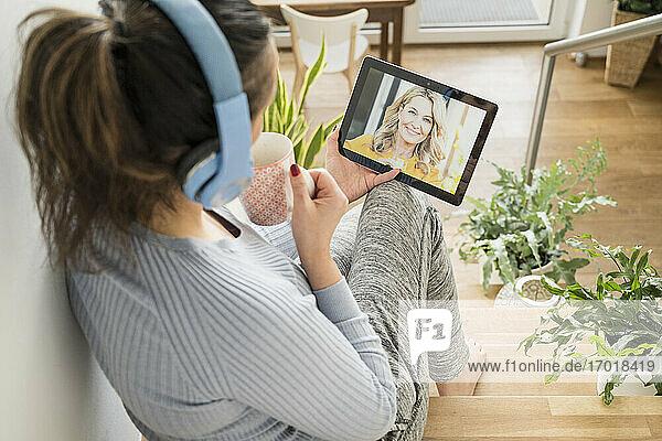 Reife Frau  die Kaffee trinkt  während sie einen Videoanruf auf einem digitalen Tablet zu Hause tätigt Reife Frau, die Kaffee trinkt, während sie einen Videoanruf auf einem digitalen Tablet zu Hause tätigt