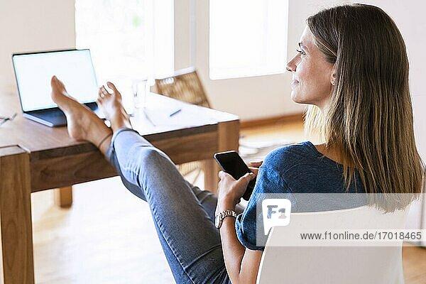 Lächelnde brünette Geschäftsfrau  die wegschaut  während sie mit Smartphone und hochgelegten Füßen am Tisch im Heimbüro sitzt Lächelnde brünette Geschäftsfrau, die wegschaut, während sie mit Smartphone und hochgelegten Füßen am Tisch im Heimbüro sitzt