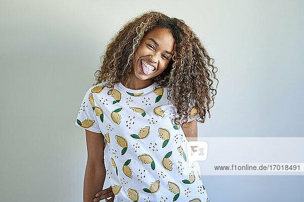 Afro glückliche Frau streckt Zunge gegen weiße Wand aus Afro glückliche Frau streckt Zunge gegen weiße Wand aus