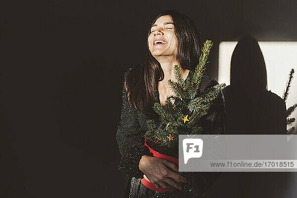 Woman with Christmas tree laughing while standing at home