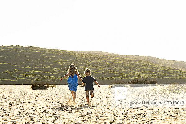 Bruder und Schwester halten sich an den Händen  während sie auf Sand laufen Bruder und Schwester halten sich an den Händen, während sie auf Sand laufen