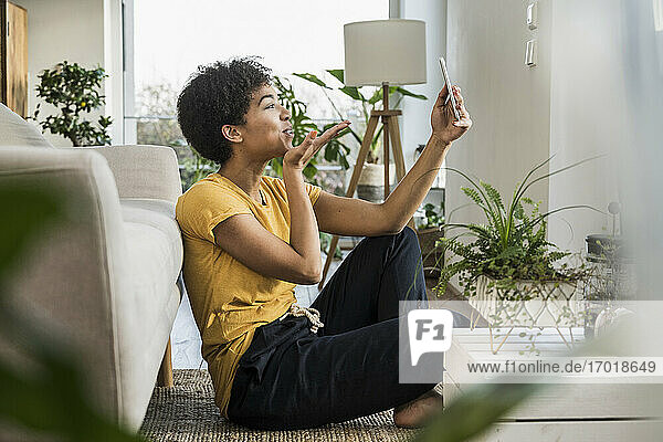 Woman blowing a kiss on video call through mobile phone while sitting by sofa at home