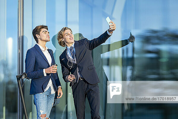 Smiling male professional taking selfie with coworker by glass on sunny day